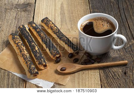 Cookies with poppy seeds and cup of hot coffee on old wooden table