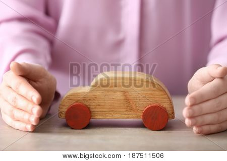 Female hands and wooden toy car on table. Travel insurance concept