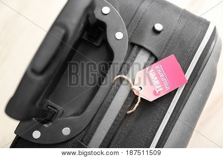 Black suitcase with label, closeup. TRAVEL INSURANCE concept