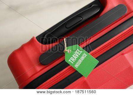 Red suitcase with label, closeup. TRAVEL INSURANCE concept