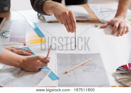 Professional drawing. Close up of a pair of compasses being held by a professional male engineer while drawing