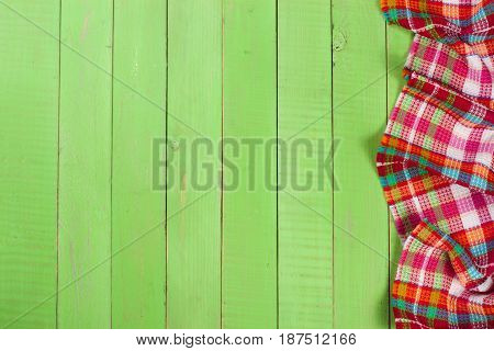Red checkered tablecloth on a green wooden table with copy space for your text. Top view.