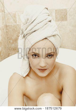 Woman sitting in bathtub.