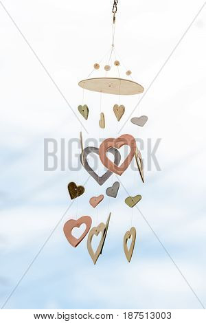 Heart shaped ceramic wind chimes hanging on window and defocused sky in background.