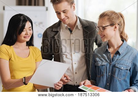 Look here. Nice delighted Asian woman holding a sheet of paper and showing it to her colleagues while standing with them