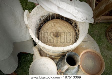 Prepared dough in medieval tub for baking bread. Medieval ware: wooden tub and ladle, ceramic pitcher and bowl.