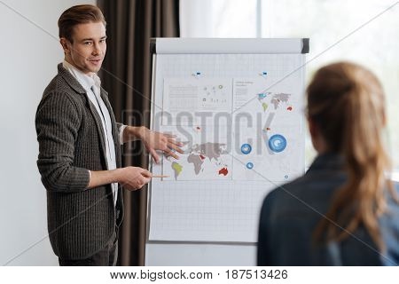 Business meeting. Handsome male office worker standing near the flip board and showing his presentation while having a business meeting