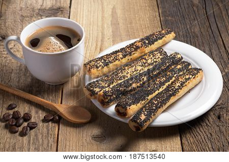 Cup of hot coffee and cookies with poppy seeds on old wooden table
