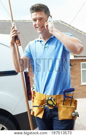 Plumber With Van Talking On Mobile Phone Outside House