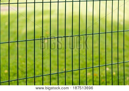 A fence of metal bars on blurred green background