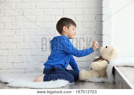 Cute little boy playing with toy bear and inhaler while sitting on floor near window. Allergy concept