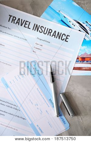 Arrival cards and pen on blank travel insurance form, closeup