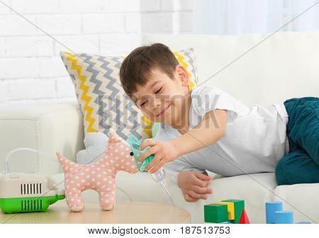 Cute little boy playing with nebulizer and toy at home. Allergy concept