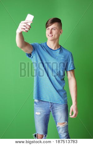Handsome young man taking selfie on color background