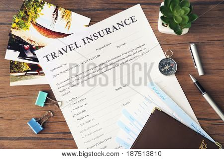 Blank travel insurance form on wooden background, closeup