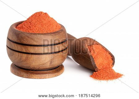 Ground paprika in a wooden bowl with a scoop isolated on a white background.