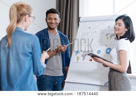 World statistics. Delighted positive handsome man holding the pencil and pointing at the documents showing the world statistics while cooperating with his colleagues