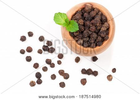Black peppercorn in a wooden spoon isolated on white background. Top view.