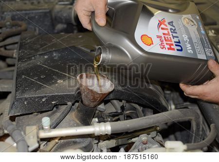 Oil Change In The Engine Of The Car. Filling The Oil Through The Funnel. Car Maintenance Station.