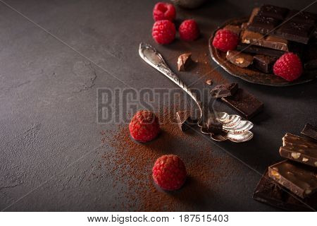 Broken chocolate pieces and raspberries on brown background with copy space. Dark photo.