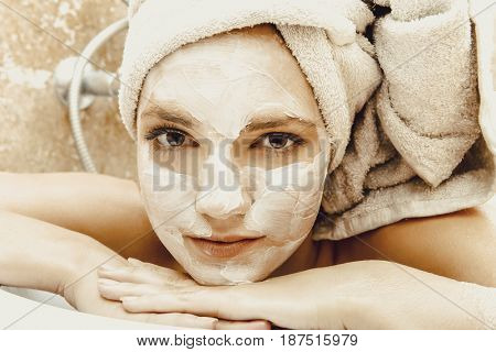 Woman relaxing in bathroom with face mask.