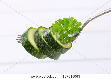 green zucchini slices impaled on metal fork