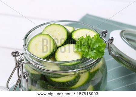 jar of green zucchini slices on grey place mat