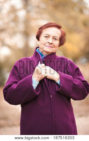 Portrait of senior woman wearing winter jacket outdoors. Looking at camera.
