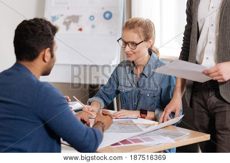 Our workplace. Pleasant smart delighted woman sitting at the table and working with drawing while cooperating in team