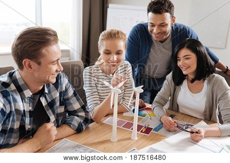 Our new project. Delighted attractive pleasant woman looking at the windmills and trying to touch one of them while sitting with her colleagues