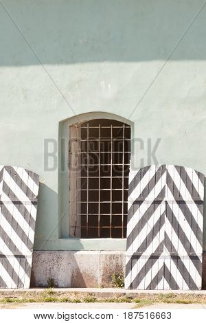 wall of prison with barred windows in clear day