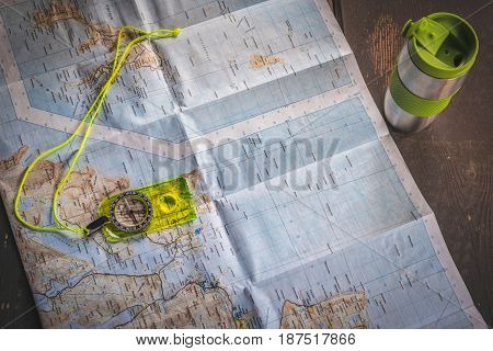 Fluorescent yellow compass lying on map of Lofoten islands Norway on wooden table next to silver thermal mug