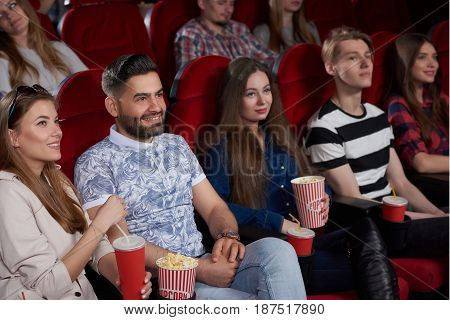 Group of best friends, couples, watching new film at modern cinema hall, smiling, having fun, eating popcorn and drinking cola. International group women and man interesting spending free time together.