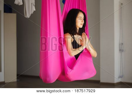 Young female person in pink hammock sitting in lotus position with attached hands and does aero yoga. Anti-gravity sport exercise
