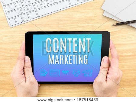 Hand Holding Tablet With Content Marketing Word On Wood Table ,internet Marketing Concept.