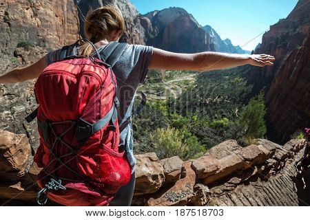 Hiker with backpack stands on the edge with raised hands and looks down at the valley