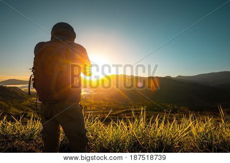 Hiker stands on the meadow with mountains on the background during sunrise