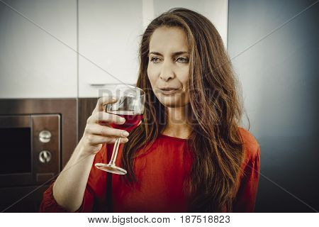 Woman with his wineglass in the kitchen.