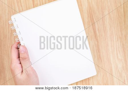 Close Up Hand Holding Empty White Open Book Above Wood Desk ,mock Up Template For Adding Your Conten