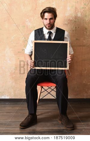 Serious Businessman Holding A Blackboard