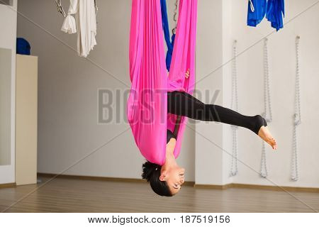 Young female person practicing inversion anti-gravity yoga position. Girl hanging on pink hammock with head below straight legs above