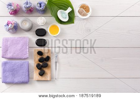 Spa treatment and aromatherapy top view background with copy space on white wood. Zen black stones, aroma salt, herbal balls for indian spa