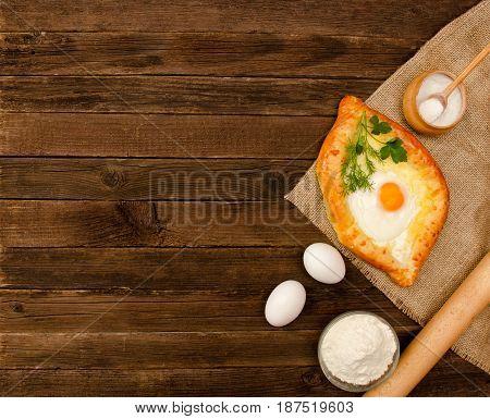 Khachapuri With Eggs On Sackcloth, Salt, Flour And Eggs On The Wooden Table, Copy Space
