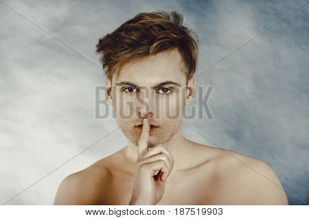 Young man showing silent gesture.
