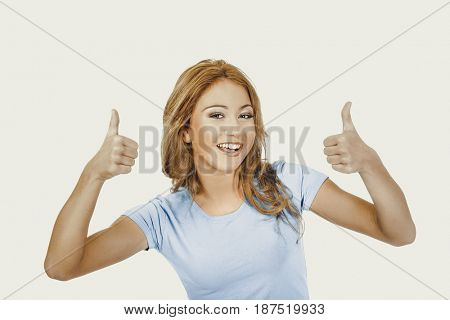 Young happy woman with thumbs up.