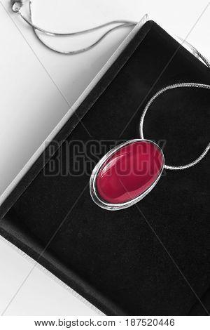 Vintage ruby medallion in black jewel box closeup