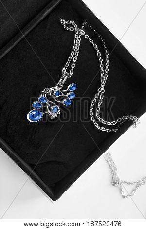 Vintage silver sapphire pendant in black jewel box closeup