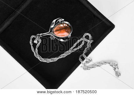Vintage amber silver pendant in black jewel box closeup