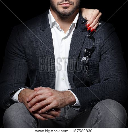 Woman hands holding handcuffs on sexy rich man shoulder bdsm