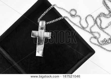 Large silver cross on a chain in black jewel box closeup